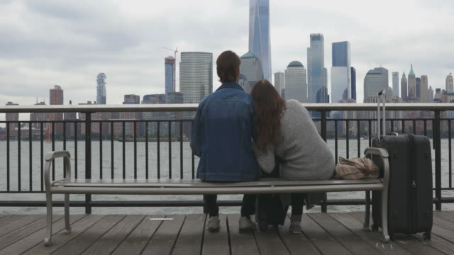 Heterosexual Couple Travelers Sitting on Bench and Waiting in New York City
