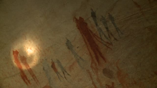 A hieroglyph of bushmen is illuminated by a flashlight. Available in HD.