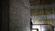 Hieroglyphics inside an Ancient Egyptian tomb Young woman walks in frame Located in the 'Valley of the Kings'