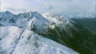 High altitude flight across a snow-covered ridge in the Spanish Peaks mountain range near Big Sky, MT to reveal Diamond Lake