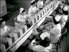 B/W high angle 1944 women with white caps packaging goods in boxes on conveyor belt in assembly line