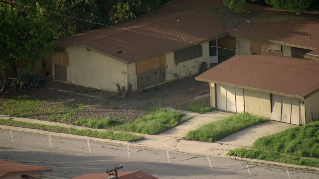 High Angle aerial push-out tracking-left - Abandoned homes fill a Los Angeles neighborhood. / Los Angeles, California, USA