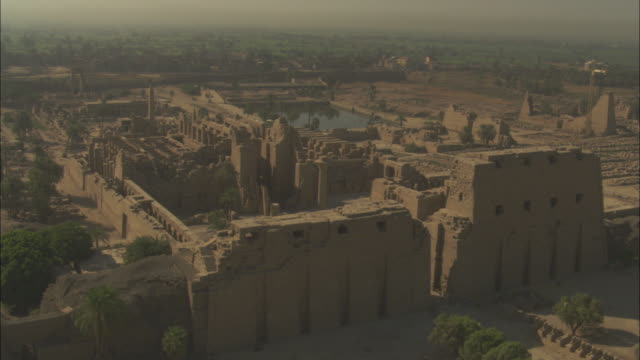 High Angle, aerial - Sandstone historical ruins with large pillars stand out in the Egyptian Nile Delta