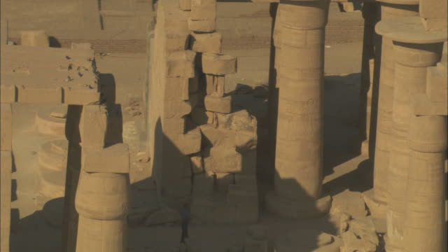 High Angle, aerial zoom-out - Sandstone historical ruins with large pillars stand out in the Egyptian Nile Delta