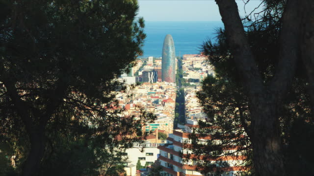 High angle Barcelona skyline seen throw the trees that are a frame for this colorful image. We can see Agbar tower and the see at the background.