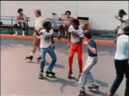 1978 high angle Black + Caucasian men on roller skates dancing in park / NYC / educational