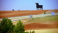 high angle bull statue on golden hillside with bus + car passing on highway in foreground / between Madrid + Seville