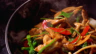 high angle close up chicken + vegetables being stir fried + flipped in pan