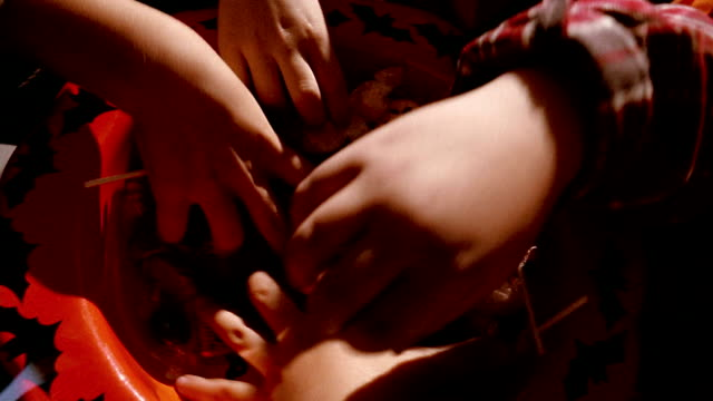 High angle close up children's hands grabbing candy from bowl