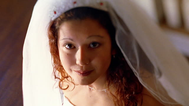 High angle close up Hispanic bride looking up and smiling