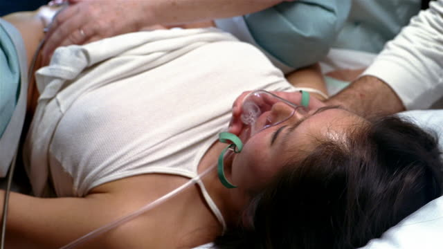 High angle close up husband holding oxygen mask on face of woman in labor / woman giving birth / Brussels, Belgium