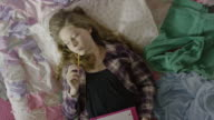 'High angle close up of teenage girl doing homework in bed / Cedar Hills, Utah, United States'