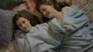 'High angle close up of teenage girls hiding under blanket during storm / Cedar Hills, Utah, United States'