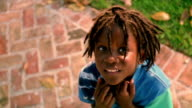 high angle close up PAN PORTRAIT Black boy with dreadlocks looking up at camera + smiling outdoors