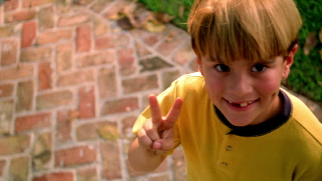 high angle close up PAN PORTRAIT blonde boy with missing teeth looking up at camera, smiling + giving peace sign