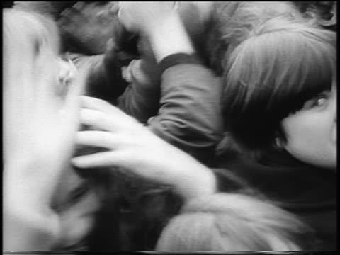 B/W 1965 high angle close up teens jumping screaming in crowd / Beatlemania / London / newsreel