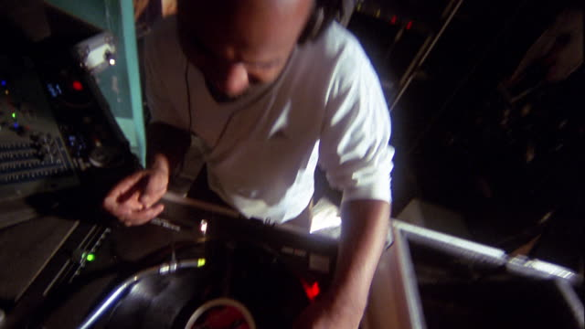 High angle close up tilt down dj scratching record and smiling at CAM