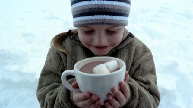 High angle close up tilt down young girl sipping from mug of hot chocolate with marshmallows / smiling at CAM