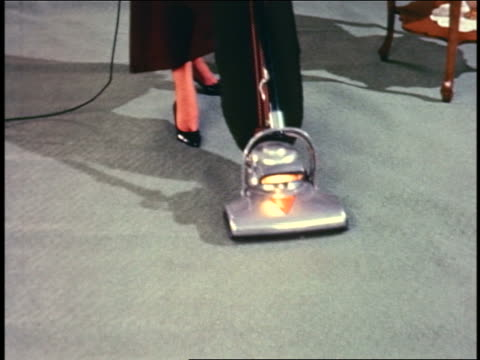 1964 high angle close up woman wearing dress pushing vacuum cleaner over grey carpet