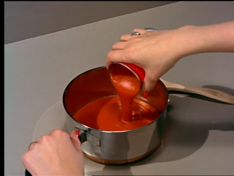1962 high angle close up woman's hands pouring tomato soup from can into sauce pan + stirring