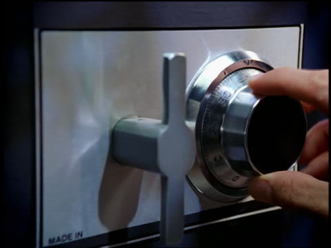 high angle close up zoom out man's hands opening combination safe, taking out passport + money + closing safe