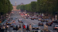 high angle crane shot traffic on Champs Elysees lined by trees with people crossing street / obelisk in background / Paris