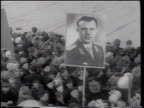 B/W 1961 high angle crowd holding poster with photograph of Yuri Gagarin / celebration of his space flight