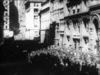 B/W 1929 high angle crowd of people walking on Wall Street / NYC / newsreel