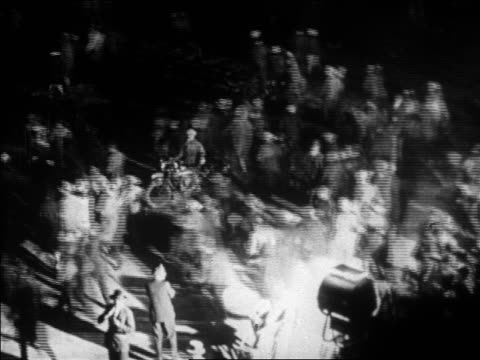 B/W 1927 high angle crowd rushing past searchlight to see Lindbergh / Le Bourget airfield Paris / newsreel