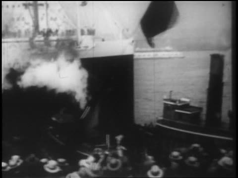B/W 1928 high angle PAN crowd waving as ship is pushed away from dock by tugboats / newsreel