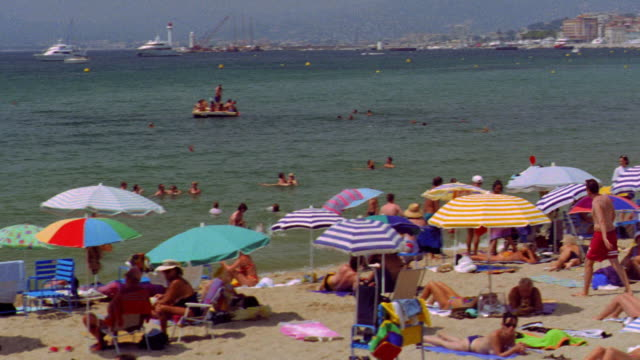 high angle PAN crowded beach with people swimming + boats in water / Cannes, France