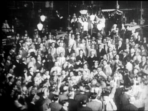 B/W 1929 high angle crowds standing on floor of New York Stock Exchange after stock market crash / newsreel
