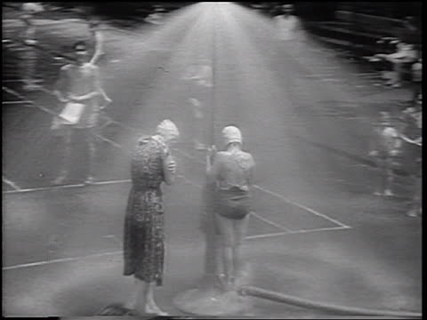 B/W 1937 high angle dolly shot children with bathing suits playing + posing for camera under sprinklers on city street
