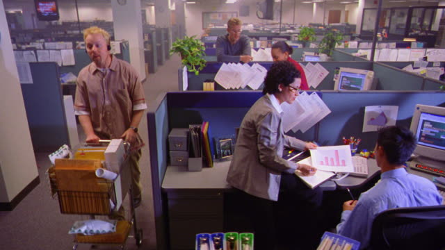 high angle dolly shot office mail man with headphones delivering mail to people talking + working in cubicles