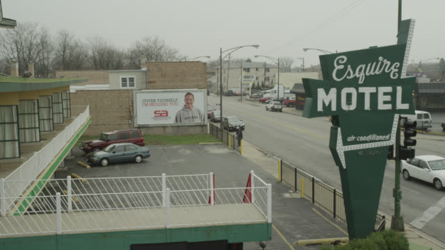 high angle down of esquire motel parking lot. lower class.