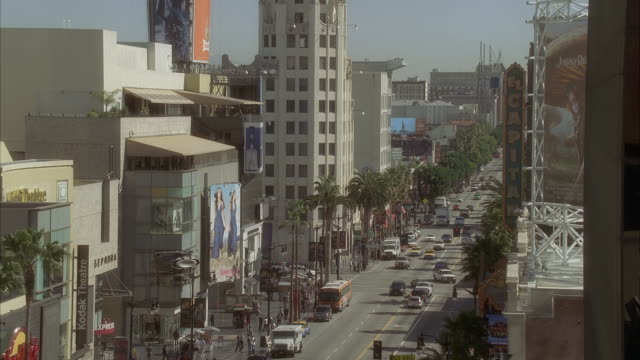 High angle down of hollywood boulevard at highland. multi-story and high rise buildings. theaters, movie theaters. hollywood walk of fame. crowds of people, pedestrians, tourists. cars on city street. landmarks. los angeles area.