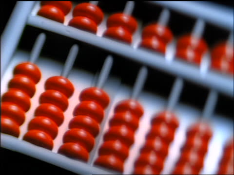 high angle extreme close up PAN abacus with red beads