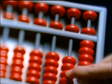 high angle extreme close up PAN hand counting on abacus with red beads