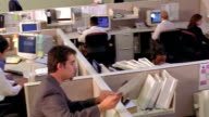 high angle PAN office workers passing envelope around in open office with cubicles / other people at computers