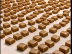 MCU High angle, Fudge squares moving along conveyor belt in factory