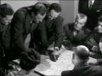 B/W 1946 high angle group of men in suits looking at map on desk + discussing it