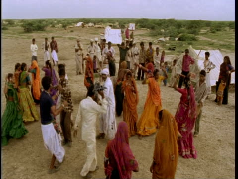 MS High angle, Gujarat, Indian Men and women dancing at desert, settlement, Gujarat, India