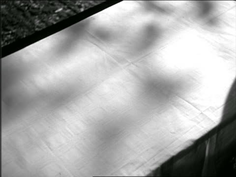 B/W 1949 high angle hands of man + woman laying tablecloth + food on picnic table
