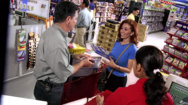 high angle MS Hispanic couple buying computer + software at checkout with female cashier