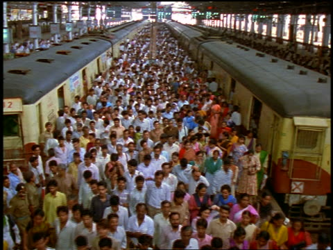 high angle huge crowd of people walking between parked trains in train station / Bombay, India