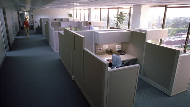 High angle INT office / woman walks down aisle / workers in cubicles