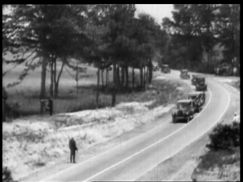 B/W 1927 high angle line of cars moving slowly past hitchhiker on country road / educational
