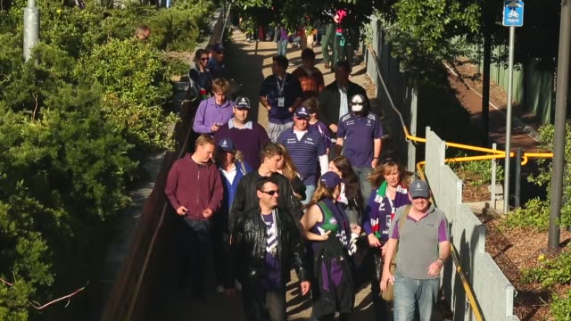 High Angle Long Shot football fans walk from the West Leederville train station to Patersons Stadium for the 2013 AFL Preliminary final between the...