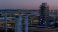 High angle long shot pan Los Angeles International Airport at dusk / pylons / Theme Building and control tower