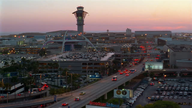 High angle long shot Theme Building, control tower and traffic at LAX at sunset / Los Angeles